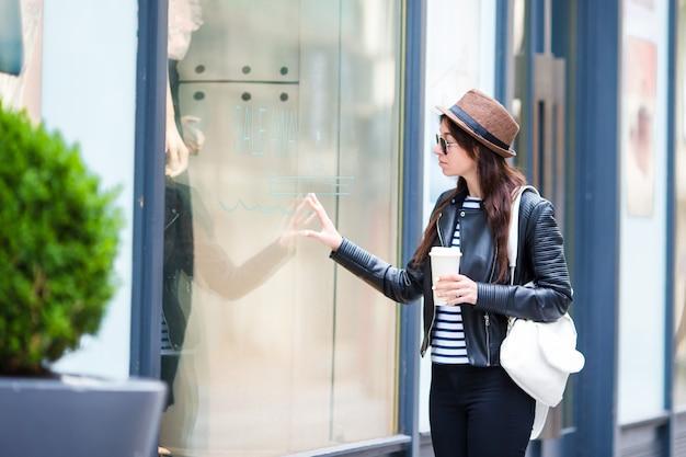 Mujer urbana joven feliz que bebe las compras del café en ciudad europea. turista caucásico con mochila caminando cerca de escaparates al aire libre