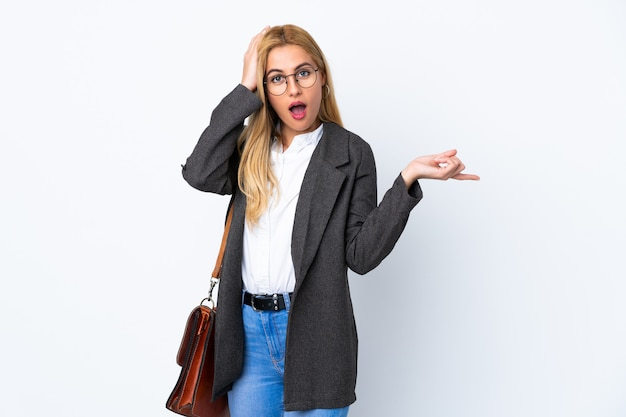 Mujer uruguaya de negocios sobre pared blanca sorprendida y apuntando con el dedo a un lado