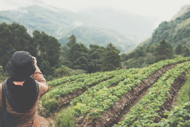 La mujer usa la cámara para tomar una fotografía de la plantación de strawberrry en la montaña.