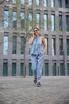 La mujer usa la conexión de roaming para comunicarse, camina por la ciudad, llama al operador para verificar el saldo de la cuenta, usa un traje de verano azul y sandalias