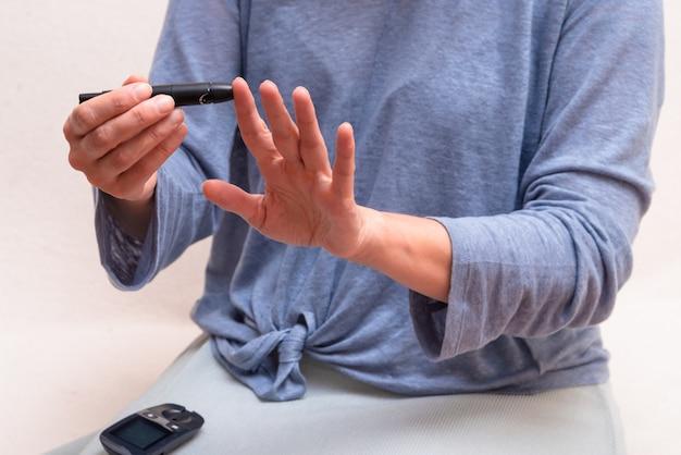 Mujer usa detector de glucosa en sangre