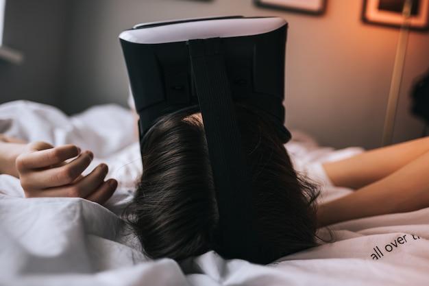 La mujer usa gafas de realidad virtual en casa, relajada en la cama. juegos, tecnologías del futuro