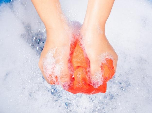 La mujer usa las manos lavando ropa de color en el lavabo con detergente tiene agua con burbujas de jabón