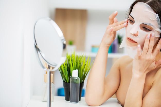 Una mujer usa una mascarilla facial en el baño