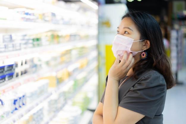 La mujer usa mascarilla protectora mientras decide elegir productos lácteos frescos para una nueva normalidad saludable