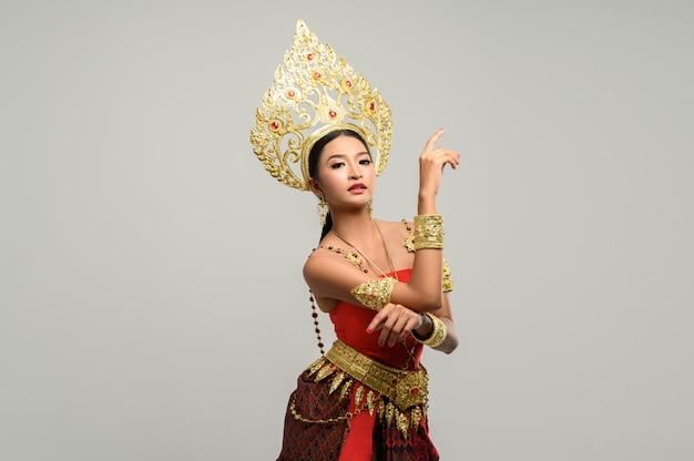 La mujer usa ropa tailandesa. la mano derecha se coloca sobre la mano izquierda.