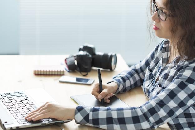 Mujer usa tableta de diseñador en el trabajo en la computadora portátil.