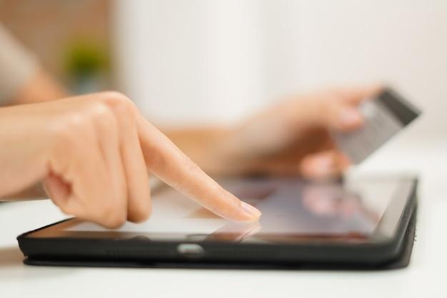 La mujer usa la tarjeta de crédito para comprar en línea y pagar la factura en tableta