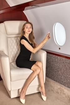 La mujer usa el teléfono dentro del avión.