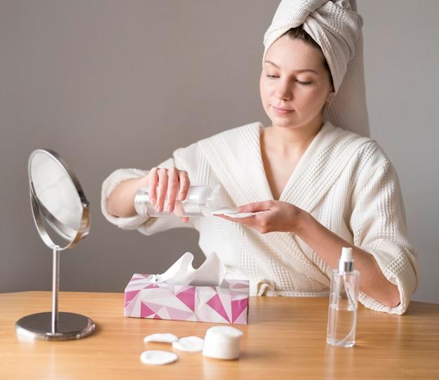 Mujer usando agua micelar para limpiar