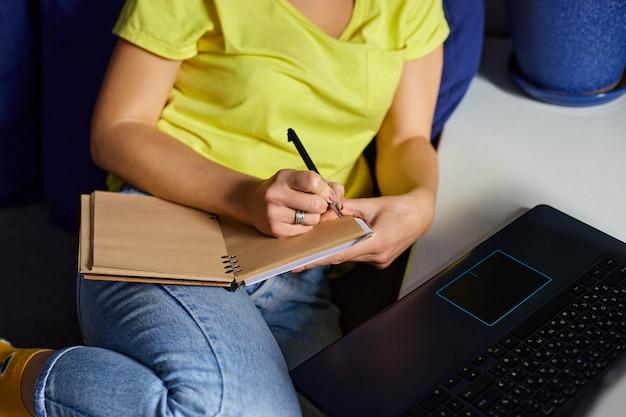 Mujer usando audífonos estudiando en línea usando notebook, laptop, escribiendo notas