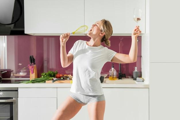 Mujer usando batidor como micrófono y sosteniendo vino
