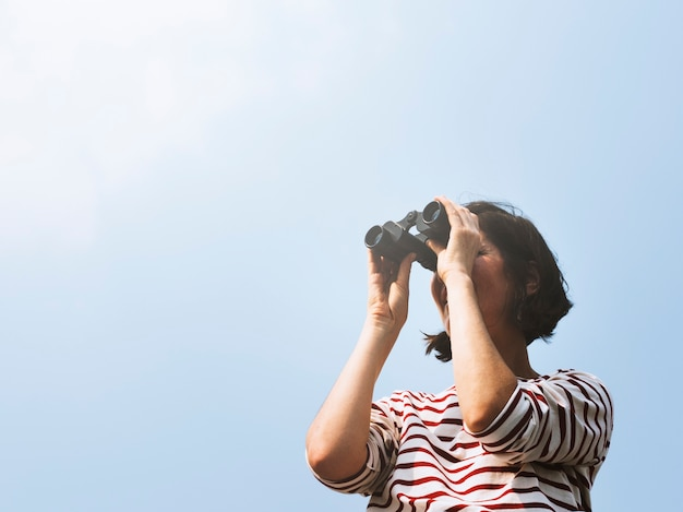 Mujer usando binoculares explorar buscando