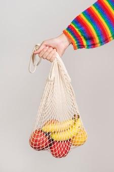 Mujer usando una bolsa de red para llevar frutas