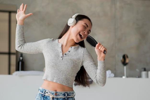 Mujer usando cepillo como micrófono