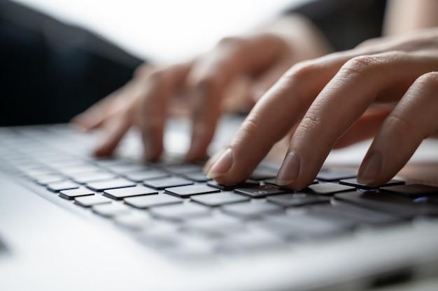 Mujer usando una computadora portátil, buscando en la web, buscando información, teniendo un lugar de trabajo en casa