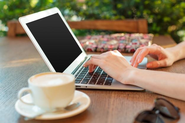 Mujer usando una computadora portátil durante un descanso para tomar café