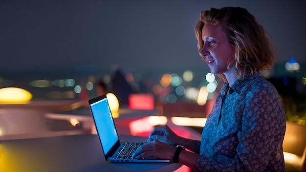 Mujer usando una computadora portátil en la oscuridad