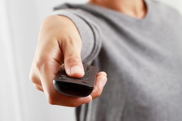La mujer está usando el control remoto para encender la televisión y ver películas en casa