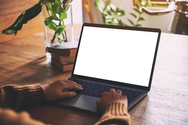 Una mujer usando y escribiendo en la computadora portátil con una pantalla de escritorio en blanco en la mesa de madera