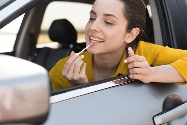 Mujer usando el espejo retrovisor para aplicar lápiz labial