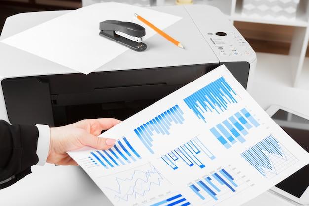 Mujer usando la impresora para escanear e imprimir documentos
