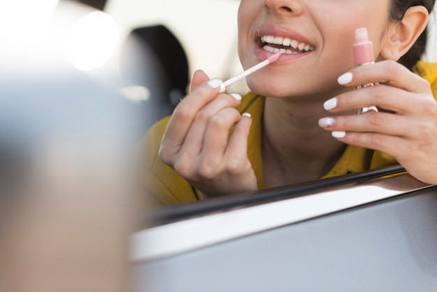 Mujer usando lápiz labial en el auto