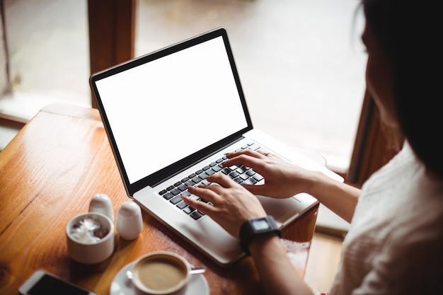 Mujer usando laptop en café