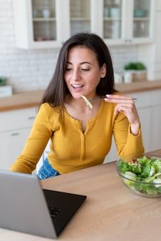 Mujer usando laptop y comiendo ensalada