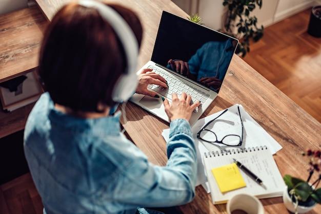 Mujer usando laptop y escuchando música en auriculares