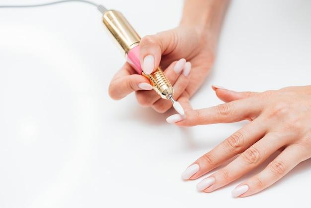 Mujer usando una lima de uñas digital alta vista