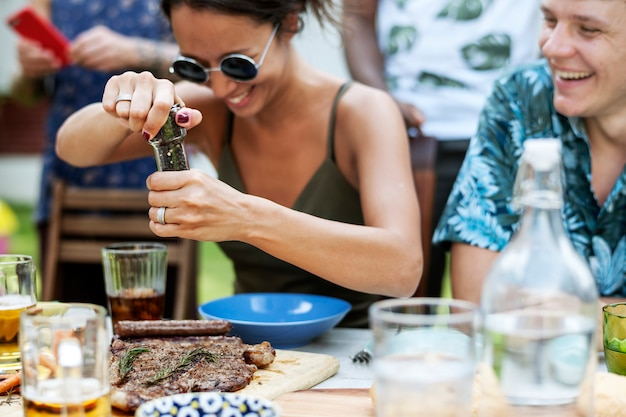 Una mujer usando un molinillo de pimienta en una comida