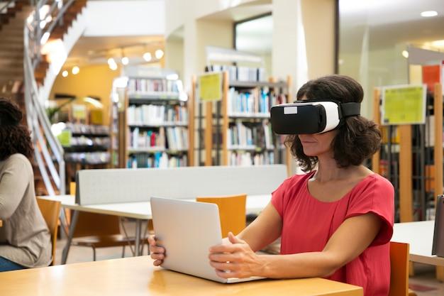 Mujer usando simulador de realidad virtual en la biblioteca