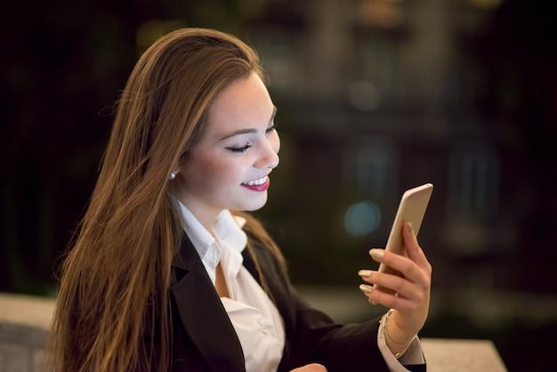 Mujer usando su celular por la noche en una ciudad