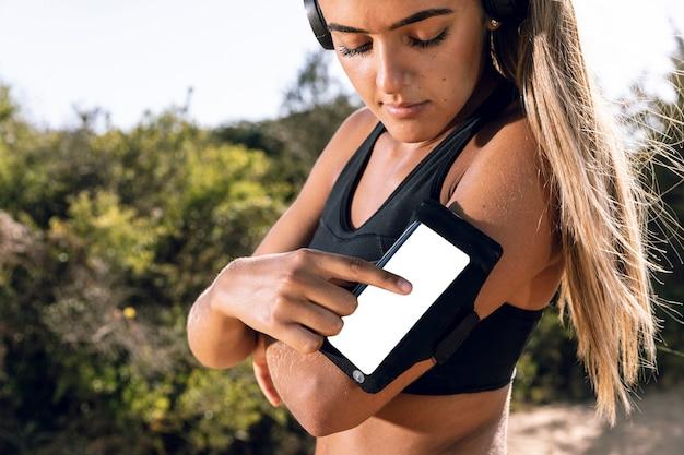 Mujer usando su maqueta de brazalete de teléfono