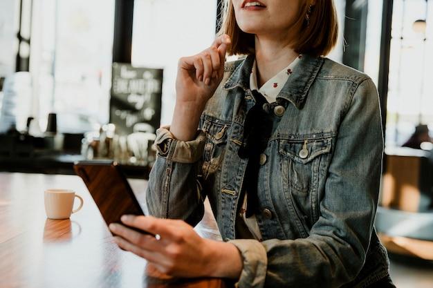 Mujer usando su teléfono en un café