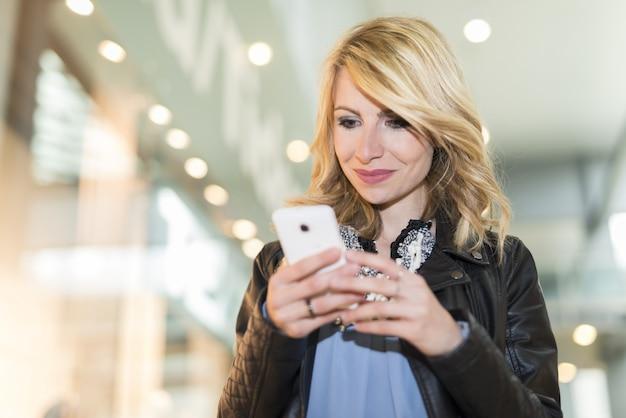 Mujer usando su teléfono móvil en un centro comercial