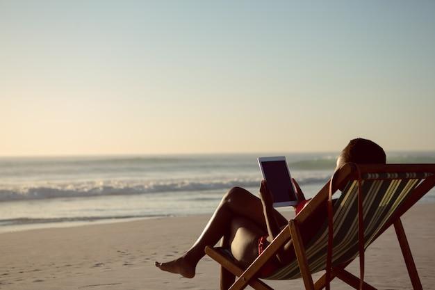 Mujer usando tableta digital mientras se relaja en una silla de playa en la playa