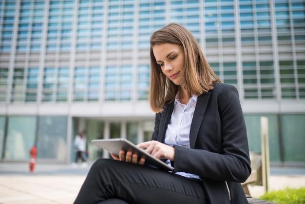 Mujer usando una tableta frente a su oficina