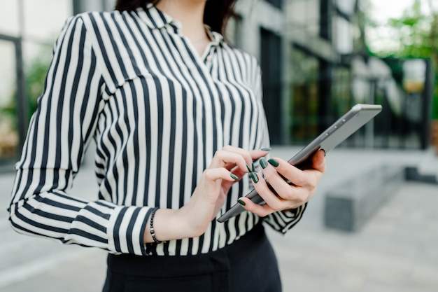 Mujer usando tableta fuera del edificio de la empresa