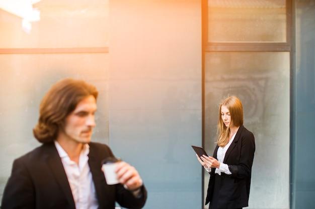 Mujer usando una tableta con el hombre fuera de foco