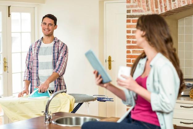 Mujer usando tableta y hombre planchando ropa en la cocina