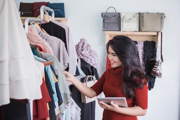Mujer usando tableta en tienda de moda