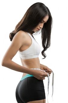 Una mujer usando un tamaño de cinta de la cintura