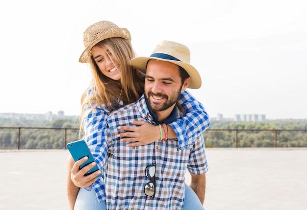 Mujer usando un teléfono celular mientras lleva a cuestas la espalda de su novio