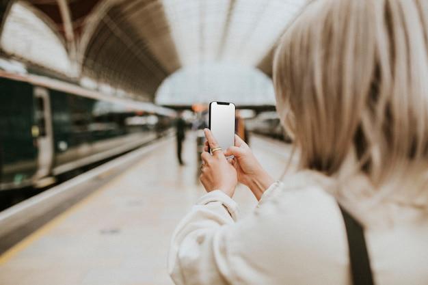 Mujer usando un teléfono en una estación de tren