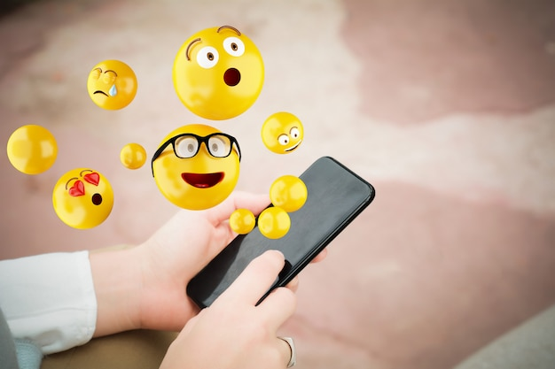 Mujer usando teléfono inteligente enviando emojis.