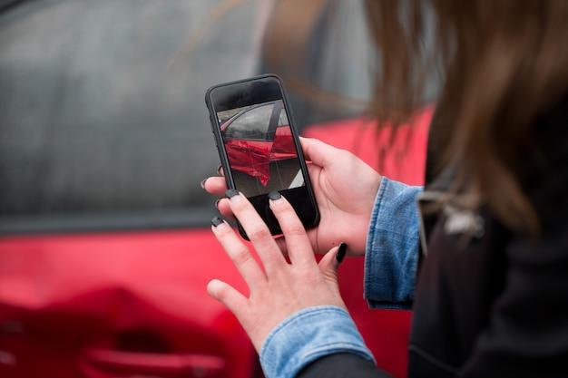 Mujer usando un teléfono inteligente para tomar una foto del daño a su automóvil causado por un accidente automovilístico