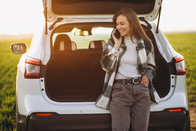 Mujer usando el teléfono y de pie junto al coche en un campo