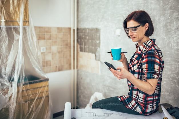 Mujer usando teléfono y tomando café mientras se renueva la cocina